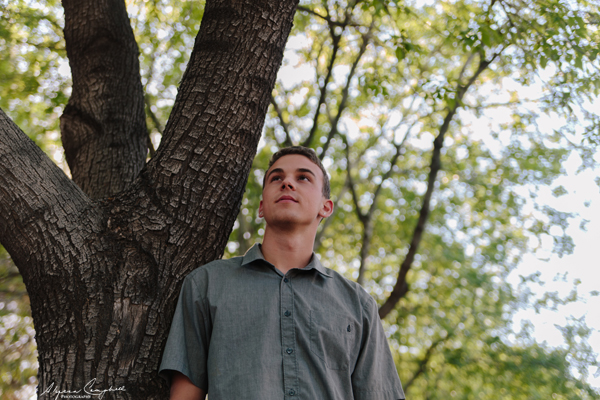 high school senior leaning against tree looking into distance
