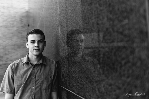 black and white senior portrait of a guy leaning against reflective wall