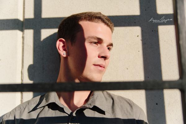 creative high school senior guy behind gate with shadows framing face