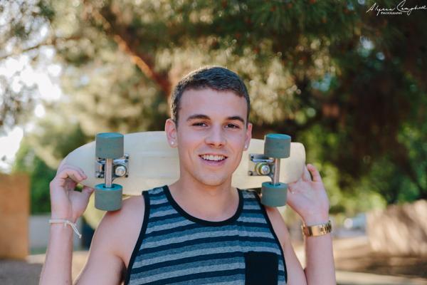 high school senior boy with mini skateboard