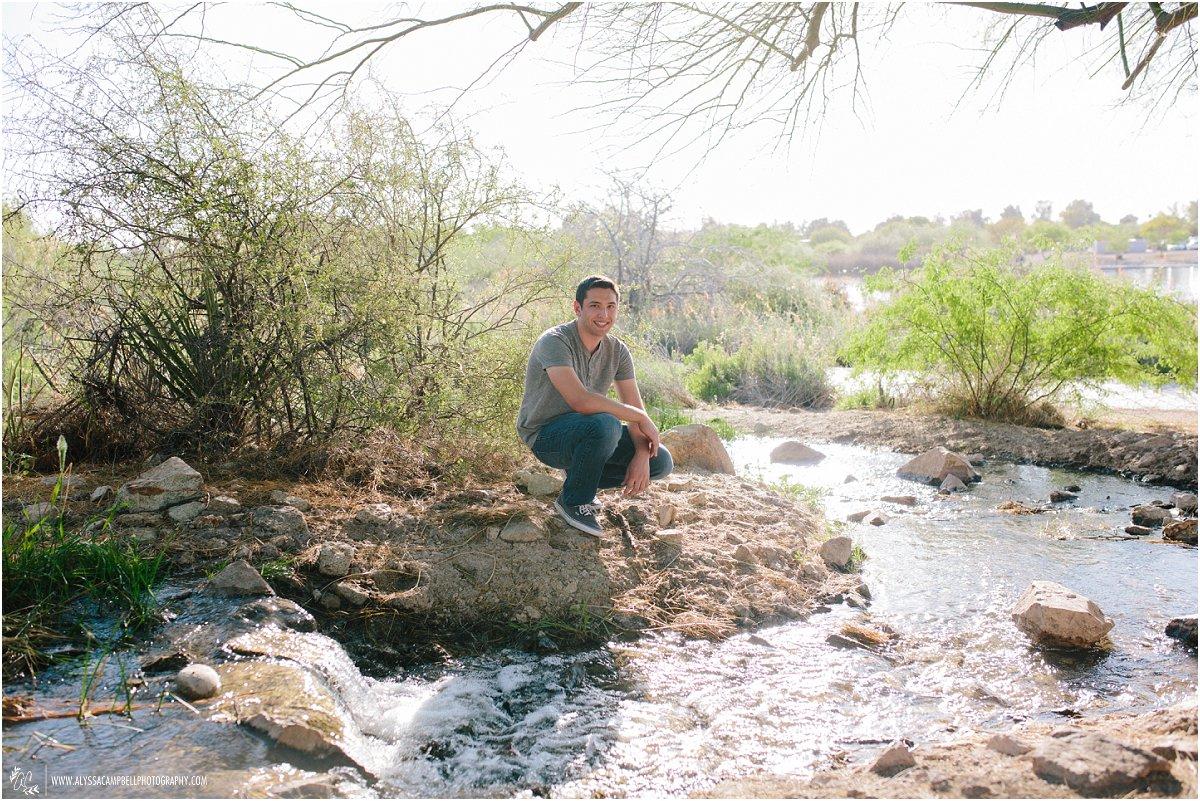 high school senior boy in grey shirt by desert stream in Arizona by Mesa senior photographer Alyssa Campbell