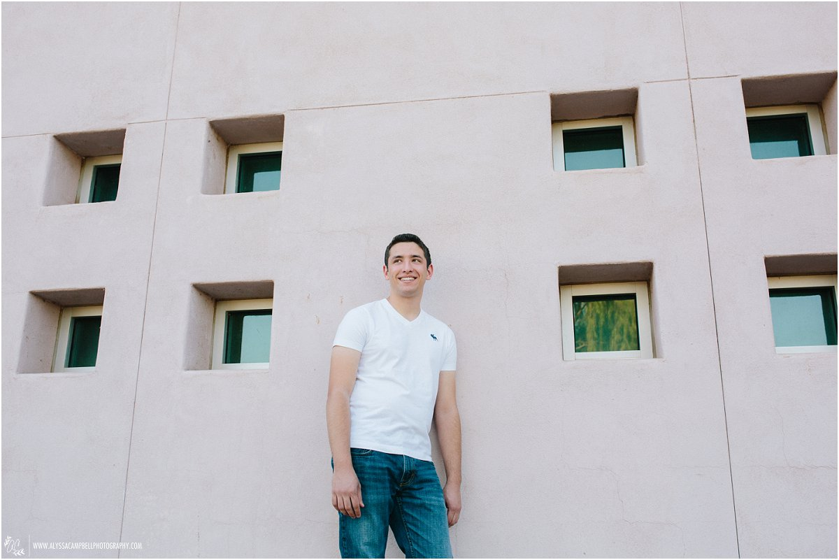 cool high school senior guy in front of windowed wall by Mesa high school senior photographer Alyssa Campbell Photography