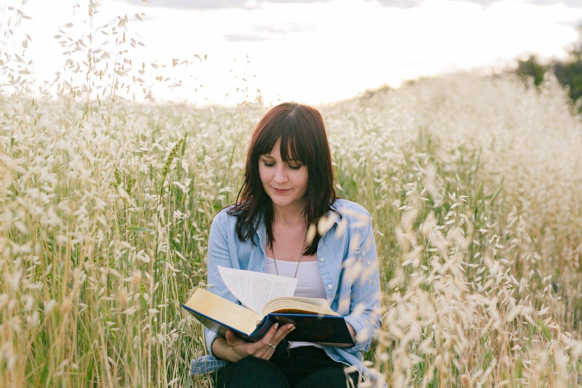 Phoenix college graduation portraits in a field reading a book