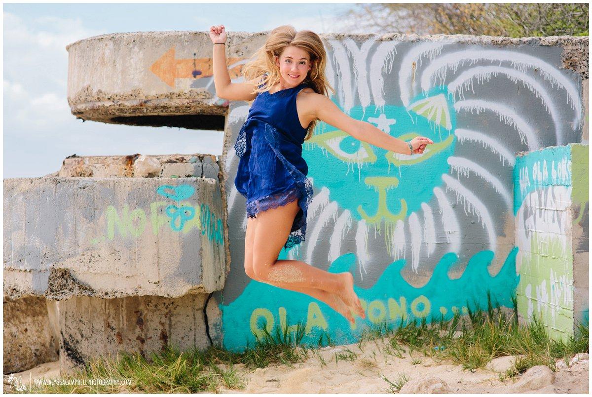 fun Oahu high school senior girl jumping graffiti wall