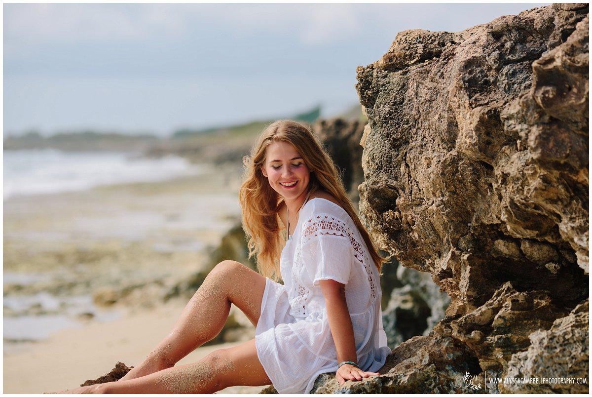high school senior girl on rocky Oahu beach laughing