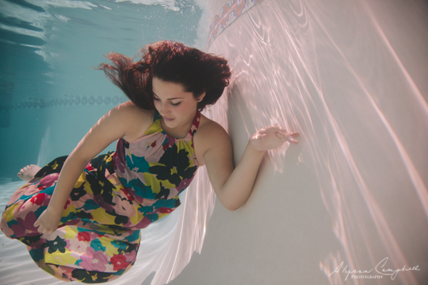 high school senior girl with dark hair in colorful print dress underwater senior session