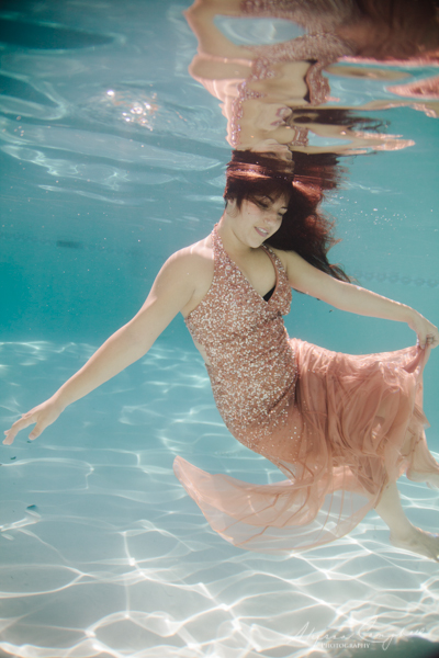 elegant underwater session with high school senior in peach prom dress with sequins dancing underwater