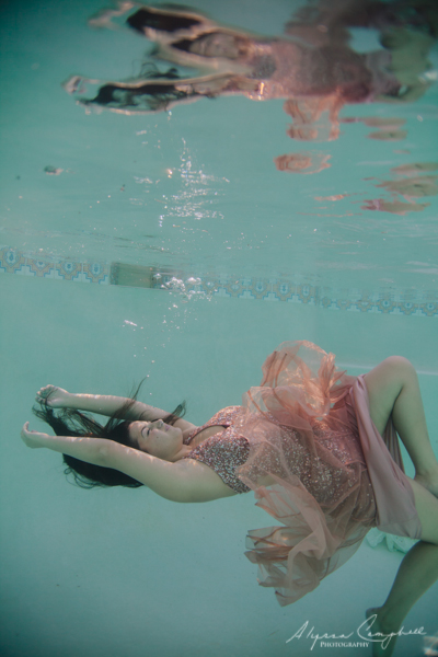 high school senior girl in prom dress underwater with arms outstretched