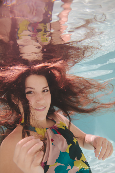 arizona high school senior girl in floral print dress underwater playing with hair looking at camera