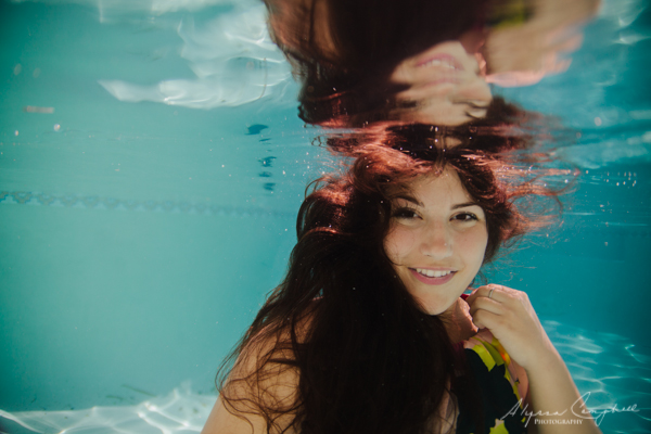 high school girl underwater with hair flowing around her smiling