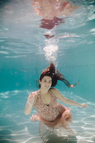 girl in peach prom dress with sequins underwater in pool