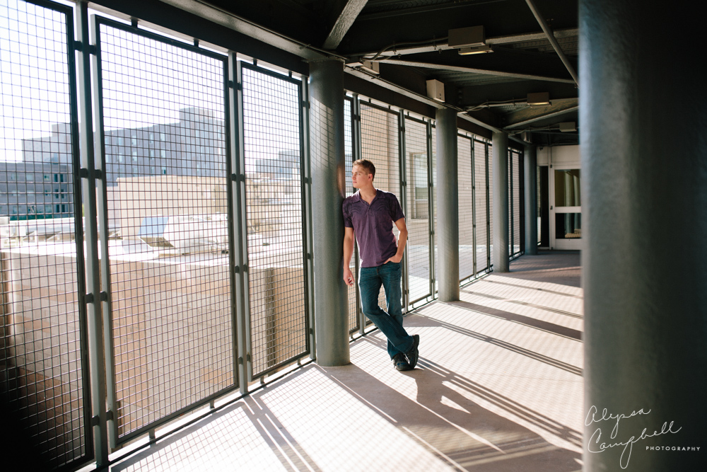 industrial portrait of college guy looking out at campus in purple shirt at Barrett Honor's College ASU