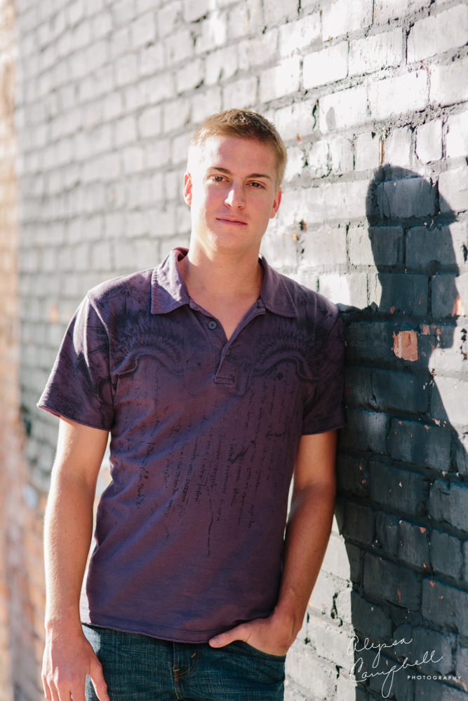 casual portrait of college guy in purple shirt against wall backlit