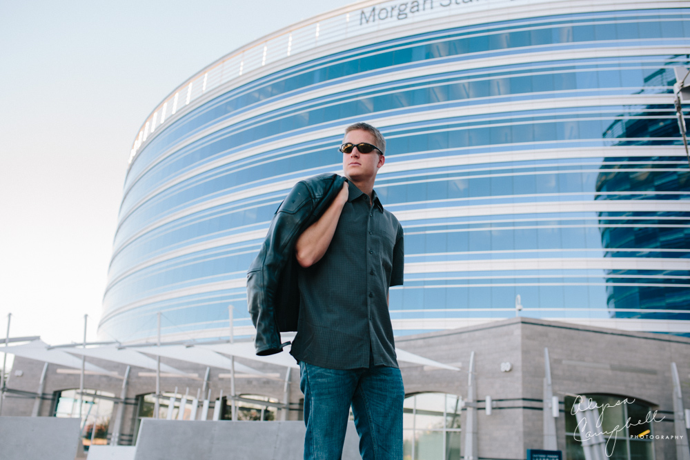 guy with leather jacket over shoulder in sunglasses looking off into distance in front of blue building