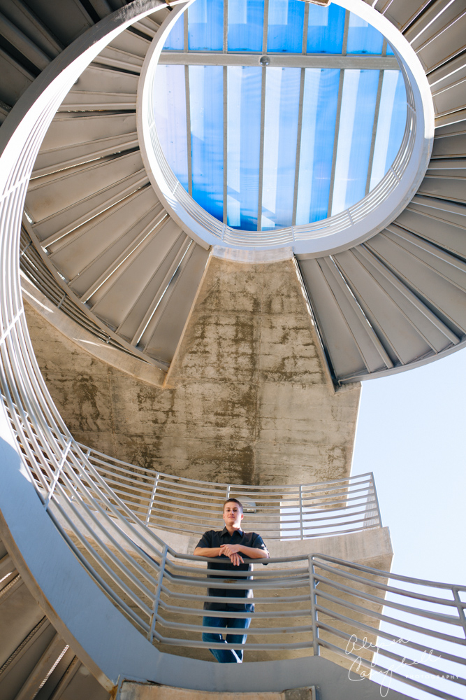 college guy in front of spiral staircase leading up to blue sky at Gammage parking lot