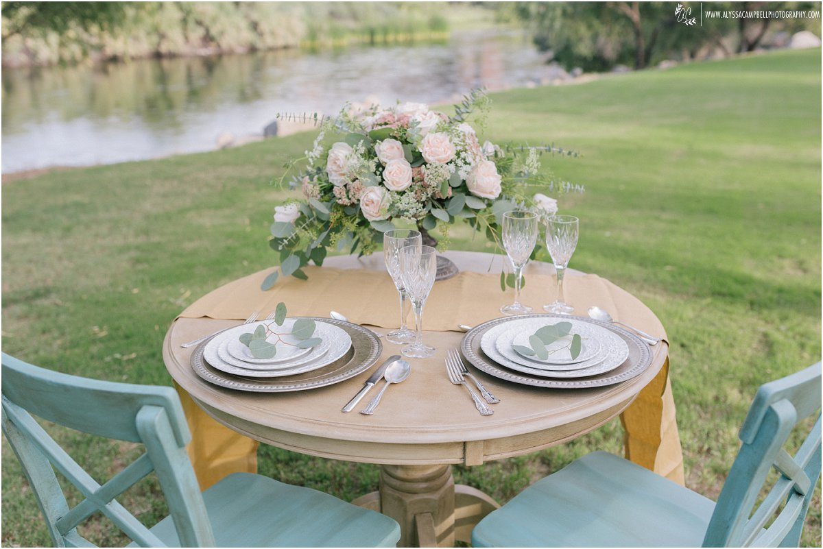 wedding table and blue chairs with fine china & yellow table runner and neutral colored florals