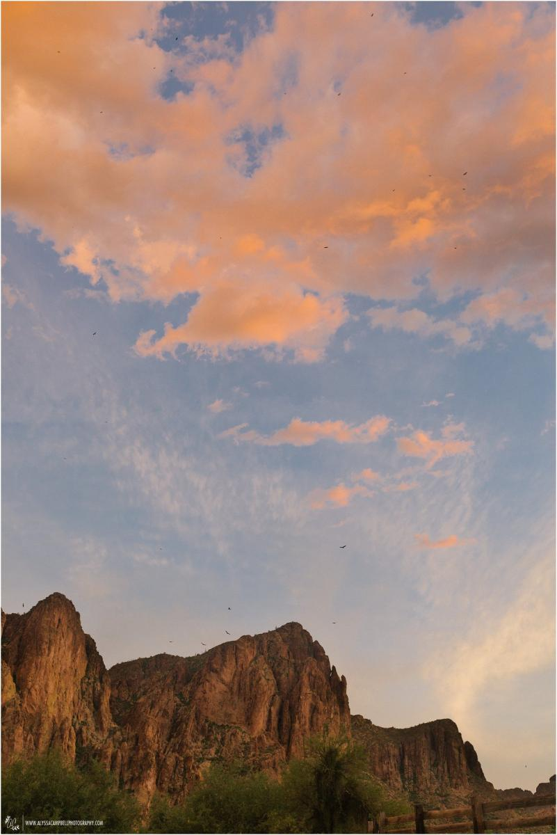Saguaro Lake Ranch and mountains lit by sunset light with birds circling overhead