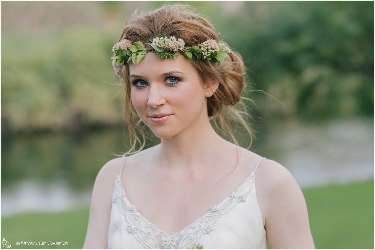 bride with beautiful blue eyes looking up wearing floral crown Mesa wedding photographer Alyssa Campbell