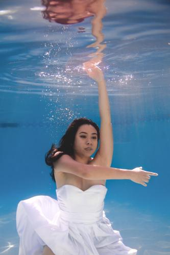 filipino bride dancing underwater in wedding dress in pool in Arizona
