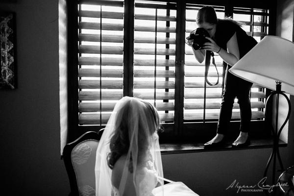 photographer standing on a window ledge photographing bride