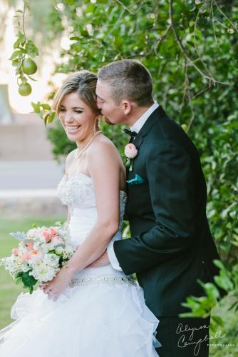 bride and groom laughing in front of citrus trees in Arizona