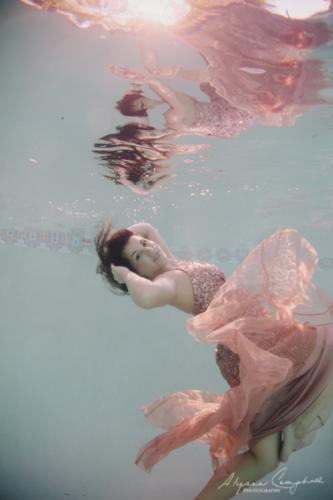 underwater photo of high school senior girl in pink prom dress in Arizona pool