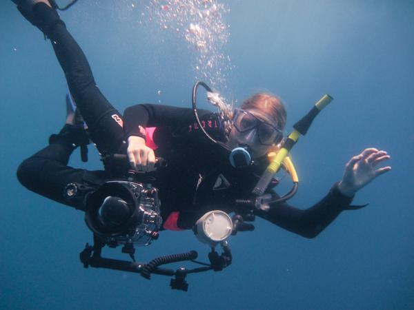 female SCUBA diver underwater with DSLR camera in Ikelite housing