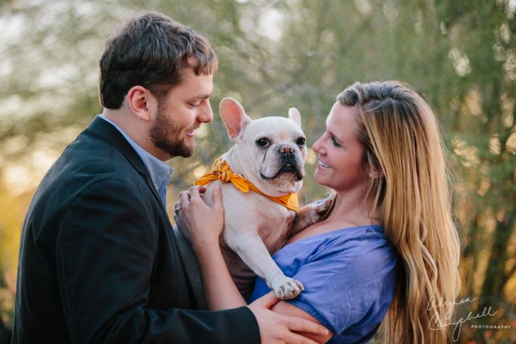 Engaged couple with their french bulldog laughing