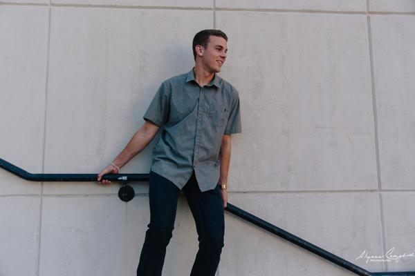 high school senior guy leaning down stair railing by Tempe high school portrait photographer Alyssa Campbell