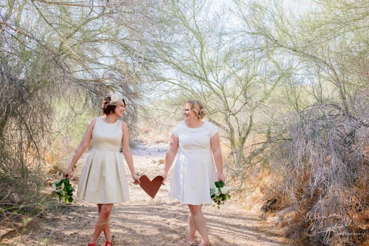 two brides holding love sign between them smiling in desert wash by Arizona LGBT friendly photographer Alyssa Campbell