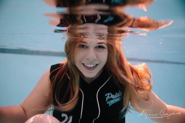 high school senior in softball uniform underwater unique underwater senior photography in Arizona