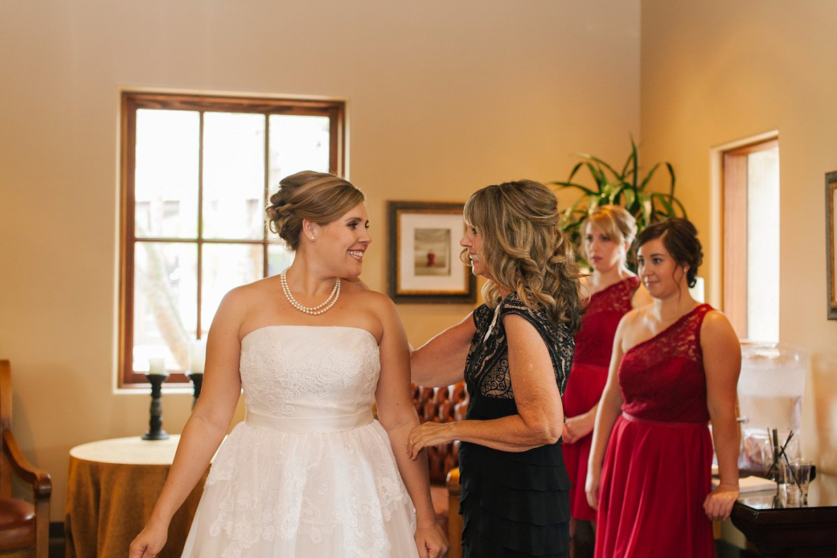 Mom helping bride into dress at Sassi Scottsdale