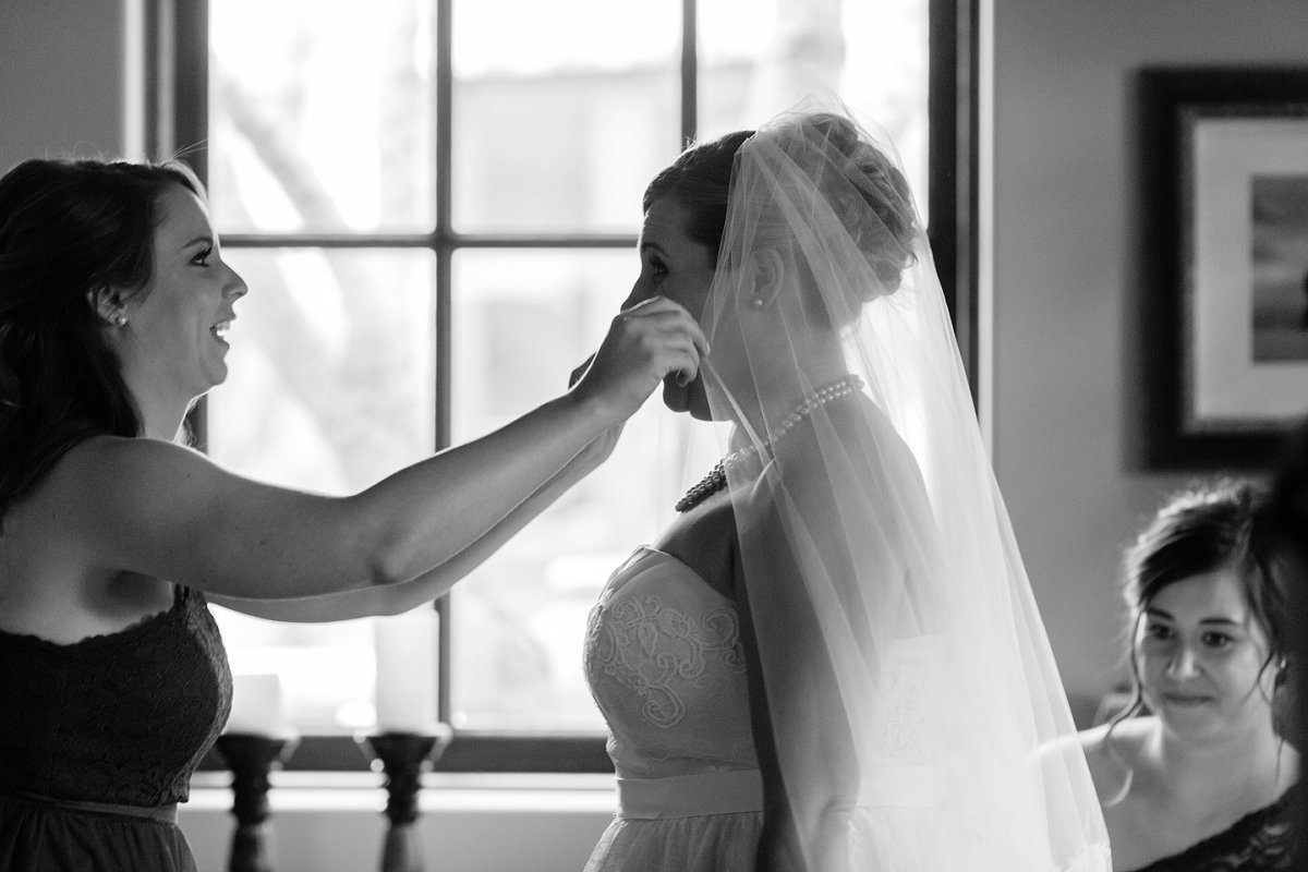maid of honor putting veil on bride at Sassi Scottsdale wedding