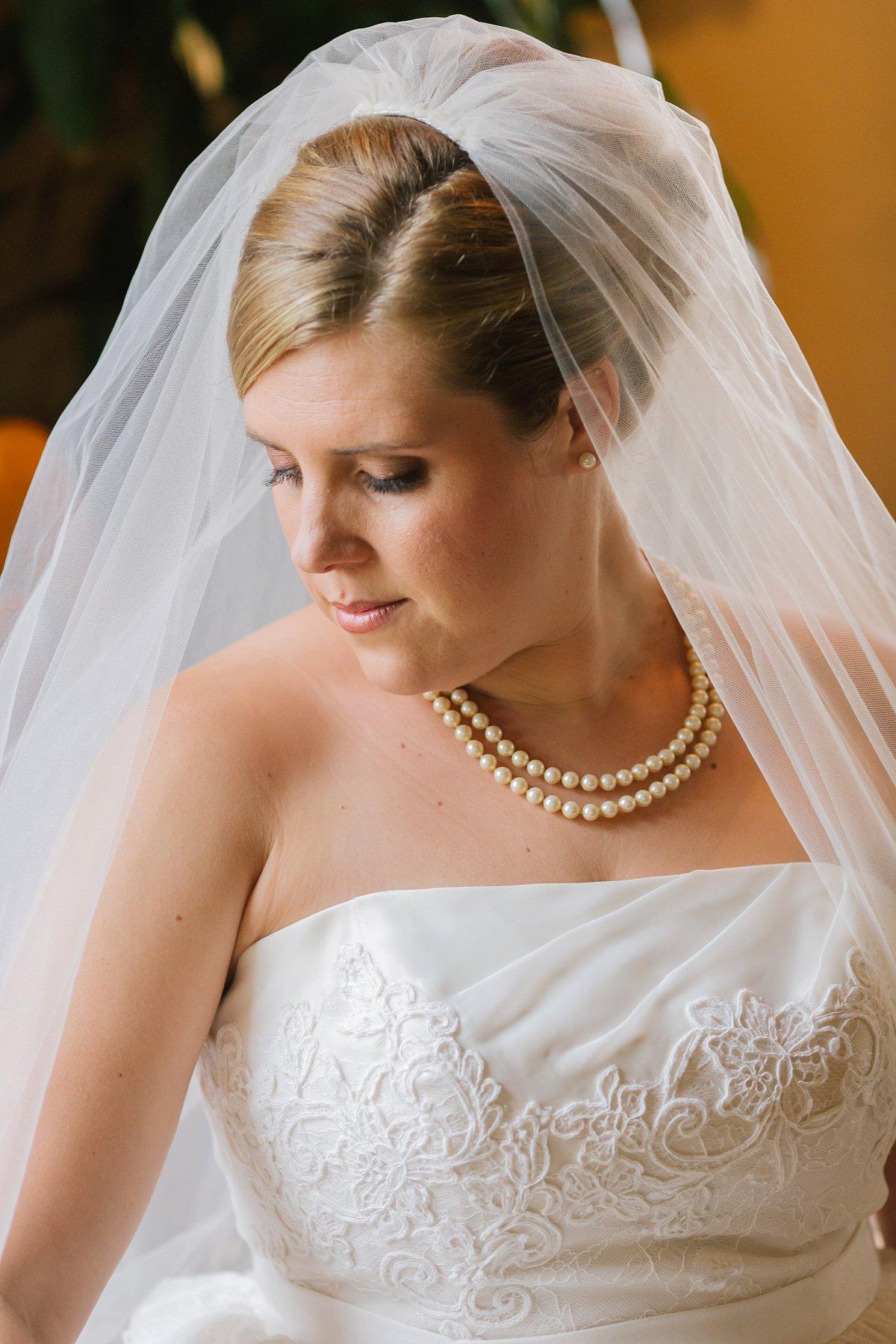 Sassi Scottsdale wedding bride looking down in window light