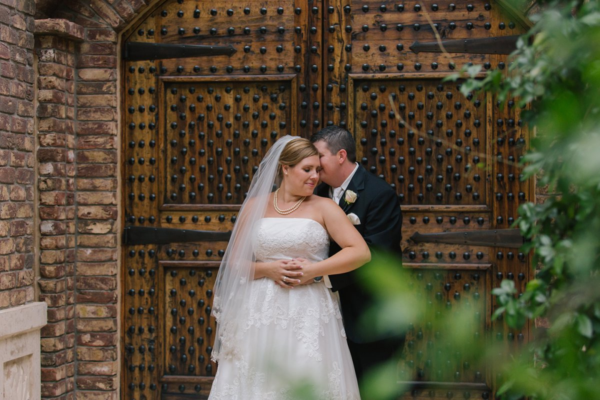 bride & groom in front of Sassi wood doors
