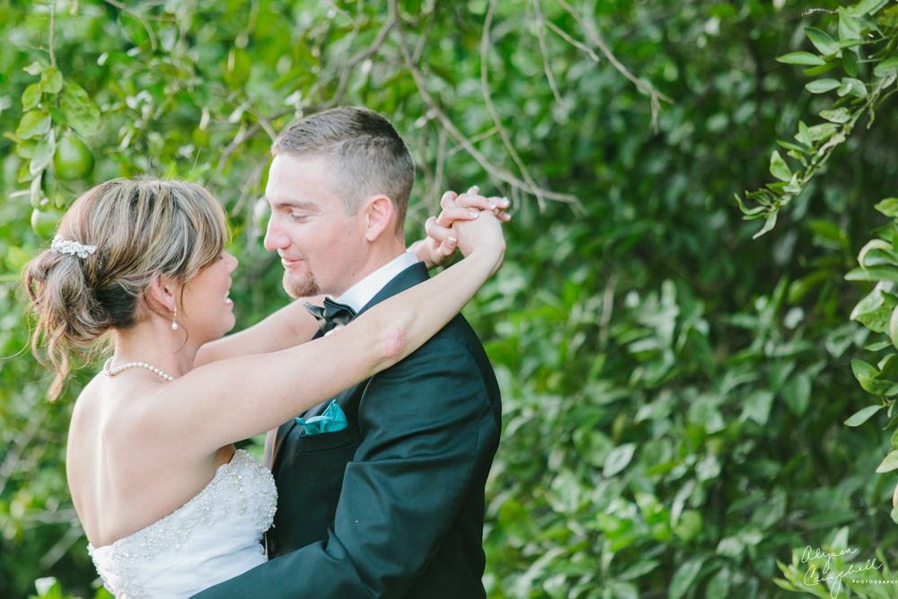 bride and groom looking at each other after ceremony in front of citrus trees