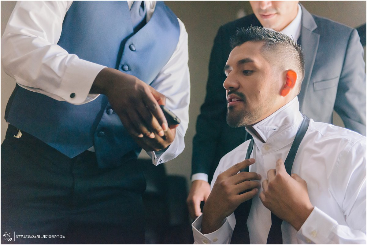 groom watching how to tie bowtie on phone in Phoenix home
