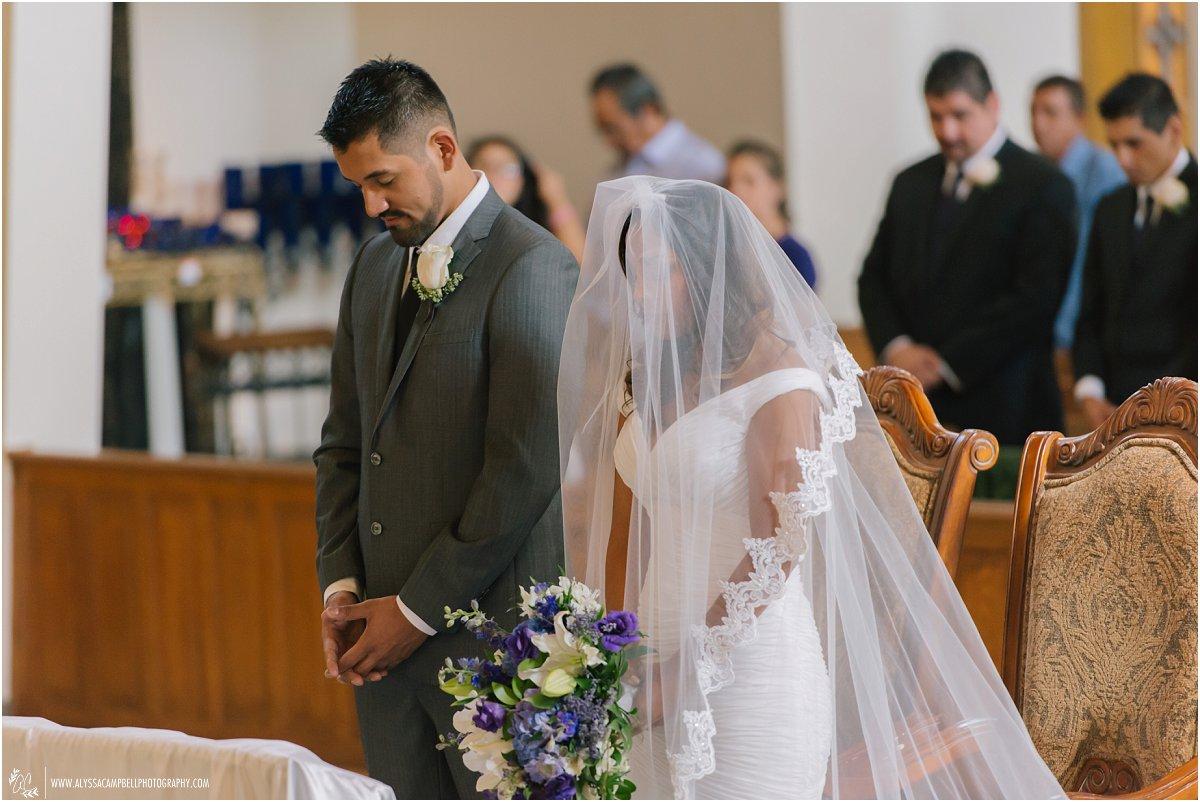 bride & groom at St Agnes church Phoenix Catholic wedding ceremony heads bowed