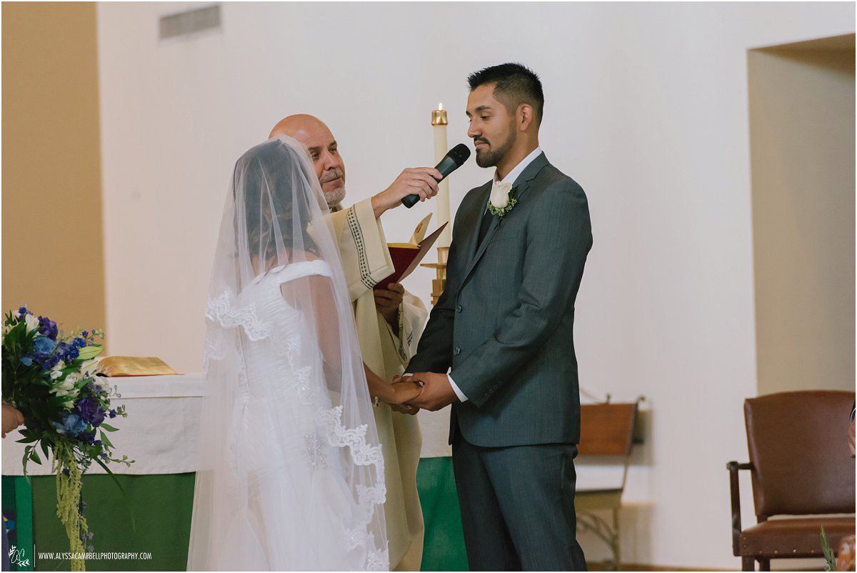 groom saying vows during Catholic wedding ceremony at St Agnes Church Phoenix