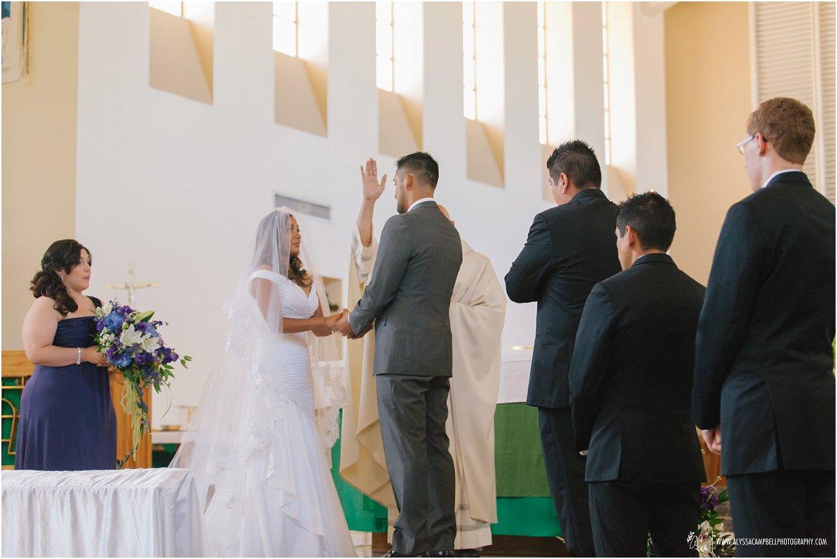 priest blessing bride & groom during Catholic wedding ceremony St Agnes Church Phoenix AZ
