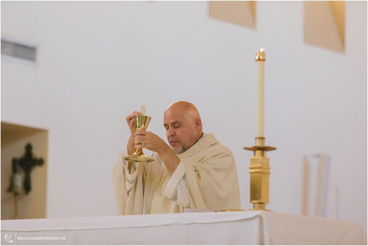 priest performing communion at wedding ceremony at St Agnes Church Phoenix AZ