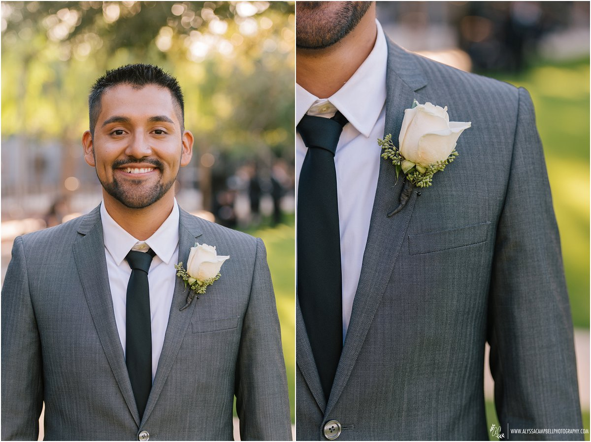 Groom in grey suit with white rose boutineer and skinny tie
