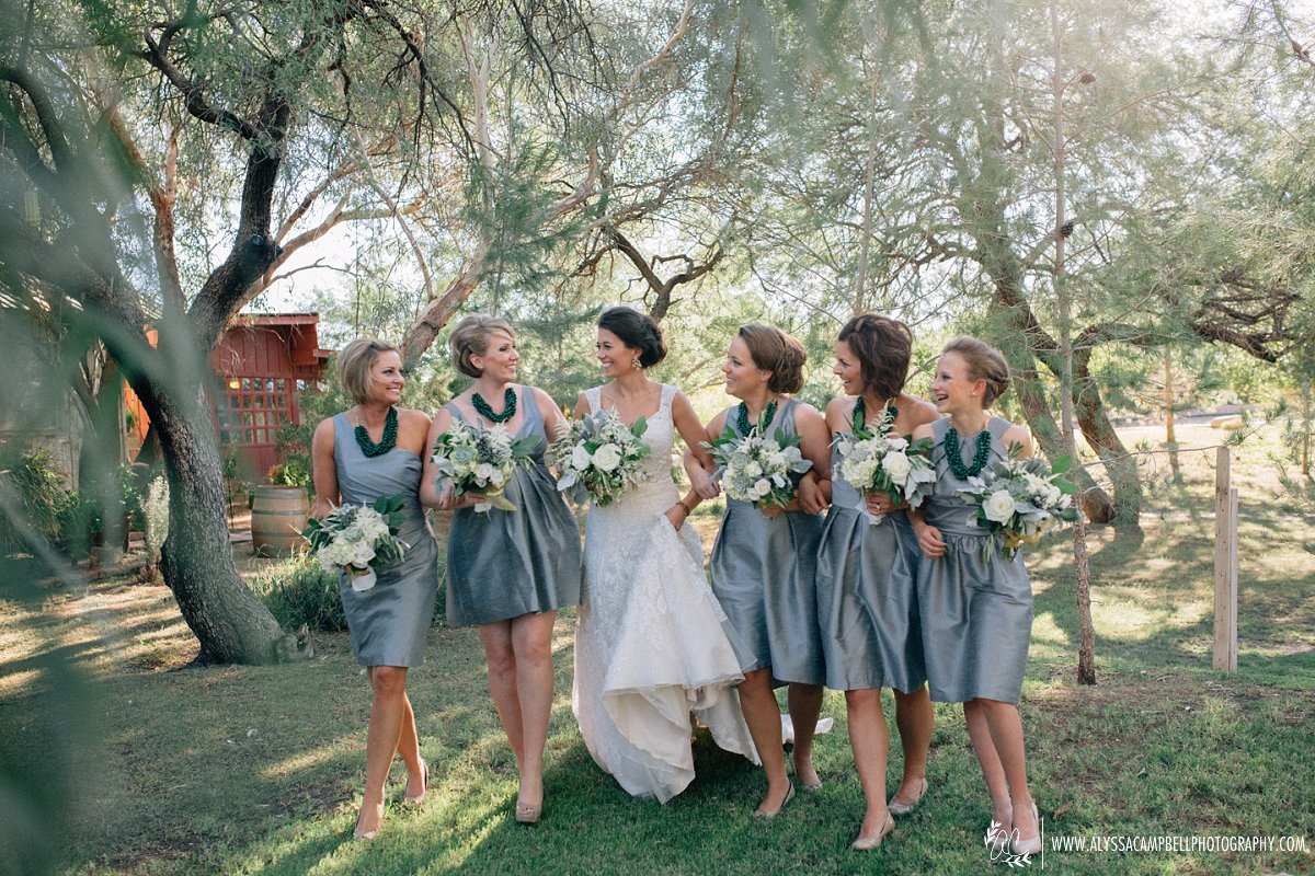 bride & bridesmaids walking and laughing together at Windmill Winery wedding venue rustic elegant barn