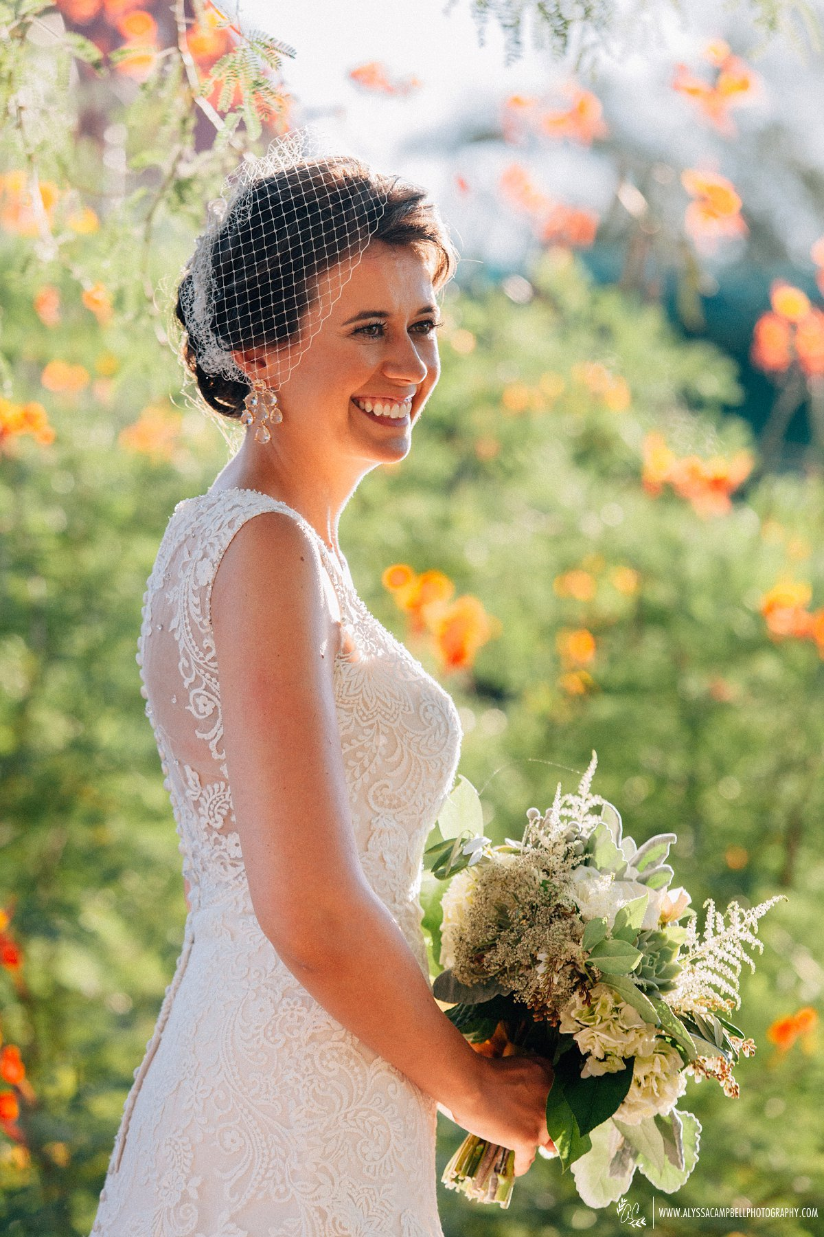 beautiful sunlit portrait of bride at Windmill Winery smiling with all over lace dress and birdcage veil