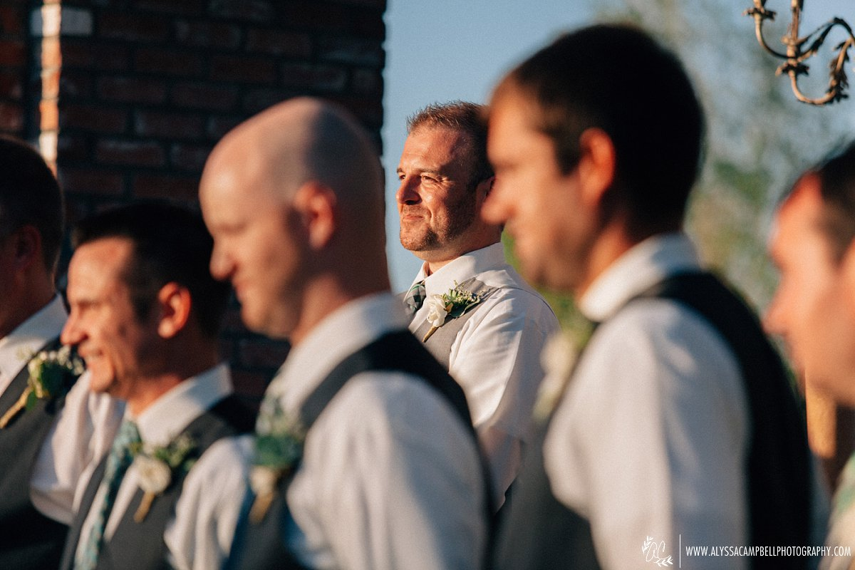 groom smiling at bride walking down aisle at Windmill Winery barn wedding venue