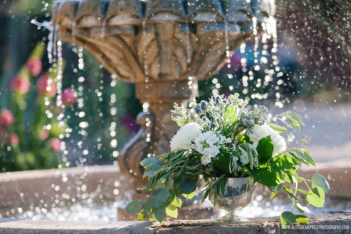 beautiful floral reception centerpiece in front of fountain at Windmill Winery by Sarah's Garden florist