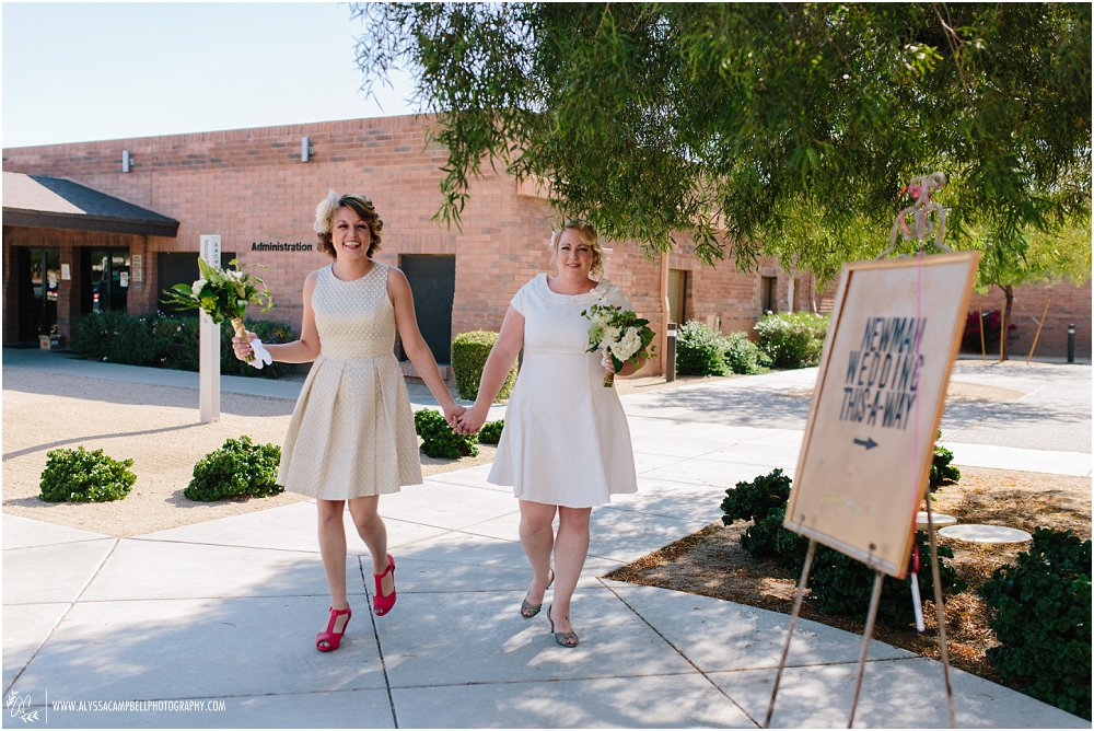 two brides in short dresses walking to ceremony at church Phoenix AZ by Arizona LGBT supportive photographer