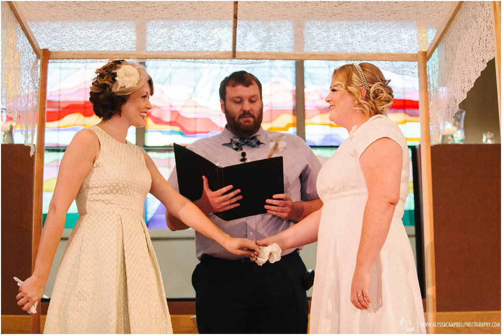 two brides holding hands in Christian wedding ceremony in Phoenix