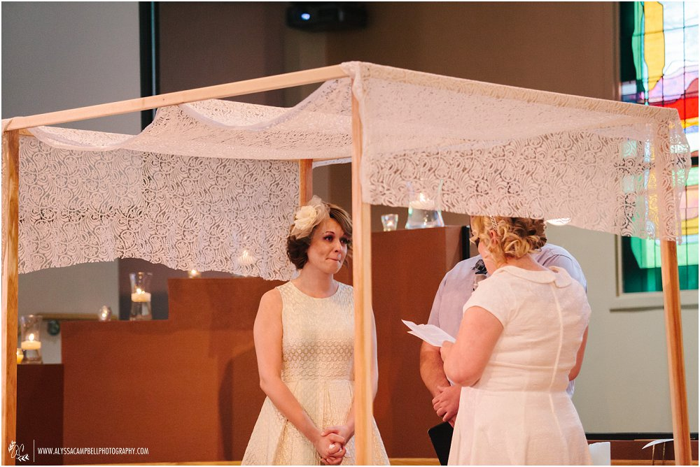 lesbian brides emotionally saying vows to each other in Christian ceremony