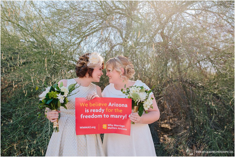 two brides looking at each other with sign about marriage rights in AZ